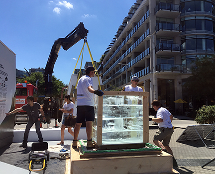 Loading ice onto the BC Building Code box platform under bright sun.